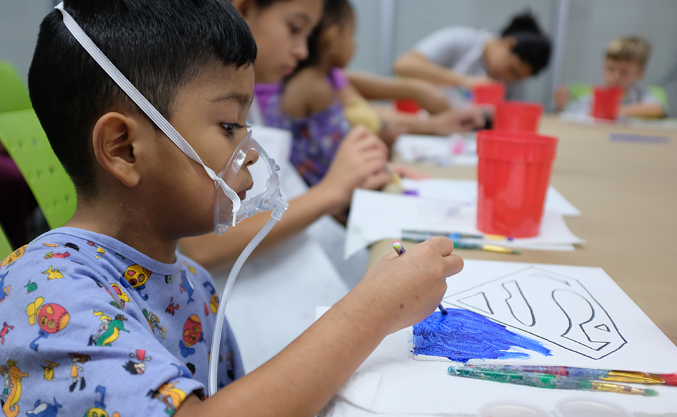 Pediatric patient is painting while attending Camp University.